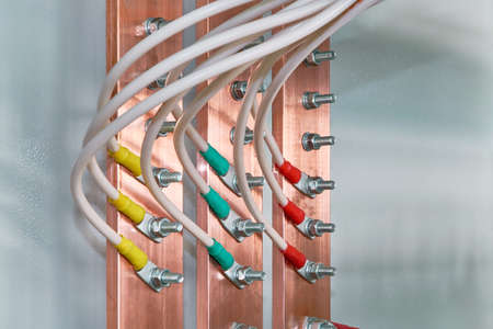 Electric bus bars connected to it by wires or cables. The cables are connected with cable lugs and nuts bolts. Accumulation and interlacing of wires or cables in the electrical Cabinet. Stock Photo