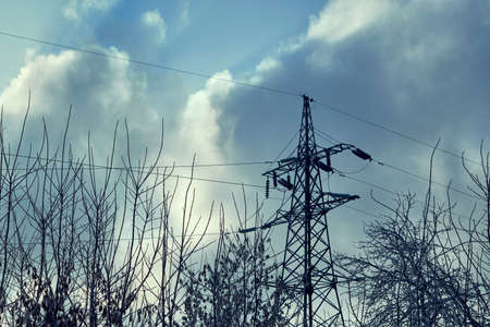 Support or tower power lines against the dark sky and tree branches. Rainy clouds, cloudy. Threat of termination of power supply. Frozen tree branches in the foreground.