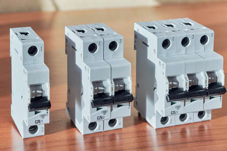 Three modular electrical circuit breakers on the table. The switch is single-pole, double-pole and three-pole. Protection of electrical wiring of household or home use. Distribution of electricity. Stok Fotoğraf - 97639273