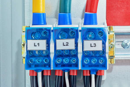 Three electrical cables or wires are connected to the distribution units. The wires are protected from touching. Allows you to avoid dangerous situations and consequences. Modern electrical equipment.