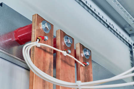Electrical wires are connected to copper busbars. Busbars are fixed to the circuit Board through red insulators. Electrical equipment is installed in the enclosure of the electrical Cabinet.
