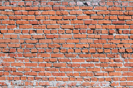 Wall of red brick. Bricks cracked. Masonry is uneven. Wall is covered or stained with cement mortar. Laying with alternation. Many layers. There are broken bricks. Background, backdrop or Wallpaper.