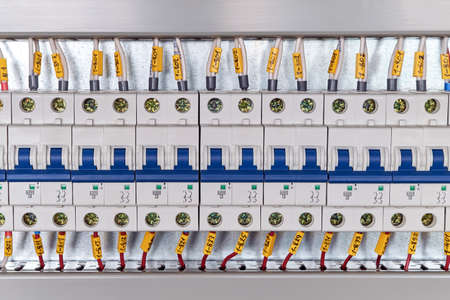 Range of electrical modular circuit breakers in electrical Cabinet. Neat and high-tech Assembly of switchboards. The wires or cables are connected to the switches and laid in the cable channels. Stok Fotoğraf