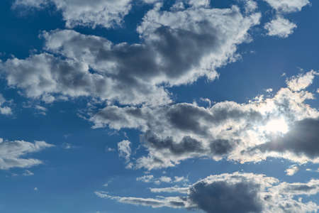 Few Cumulus clouds blotted out the sun. The sun's rays breaking through a cloud with ragged edges. Atmosphere before the rain. Background, backdrop or Wallpaper. The sun hid.
