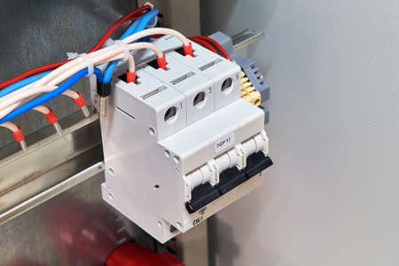 Circuit breaker with connected wires or cables in electrical Cabinet. The switch is fixed on a special metal rail. The electrical wires are tied into a bundle by a plastic coupler.