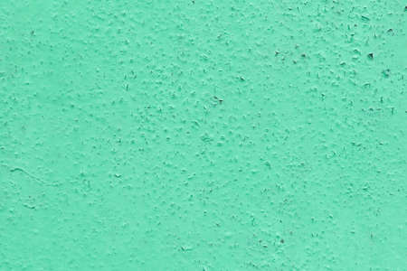 The wall surface is painted with oil paint. The paint cracked with time and weather. On the surface of the cracked swollen bumps. Wall with dots and stripes. Texture or background. Stock Photo