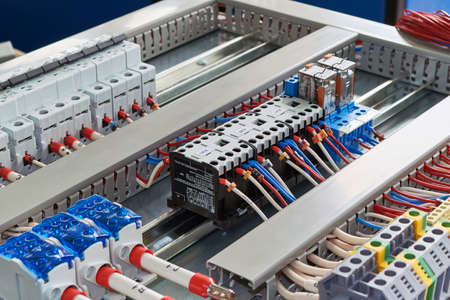 Contactors, relays, circuit breakers and terminals in the electrical Cabinet. Electrical wires or cables are connected to electrical equipment according to the project. Modern technologies, design. 版權商用圖片