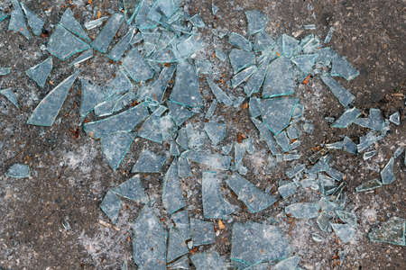 Lying on the ground a lot of sharp fragments of broken glass. Glass fragments of different shapes and sizes. Broken glass is a bad sign. Abstract background or backdrop. Banque d'images