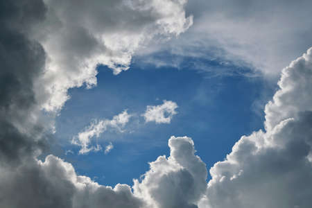 Stormy Cumulus clouds are surrounded by a clear blue sky. In the middle of an oval of clear sky and hovering around all sides of the rain clouds. Meteorology, weather forecast. Stock Photo