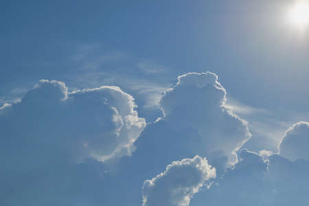 The sun shines brightly in the clear blue sky. Big storm clouds are coming. Cumulus clouds before rain looming on the sun and want his shield. Sunlight and rays illuminate the sky and clouds.