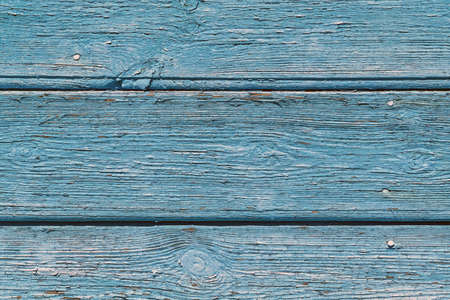 The surface of old wooden boards painted by blue paint. The paint faded and disappeared in the open air. The paint swelled and burst, covered with small cracks. Background, backdrop, Wallpaper. Imagens