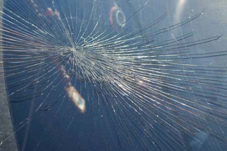 Cracks from the impact on the windshield of the car. The cracks radiate from the center of the impact. Collision with flying stones on the road. Risk and danger of damage. Robbery or vandalism.