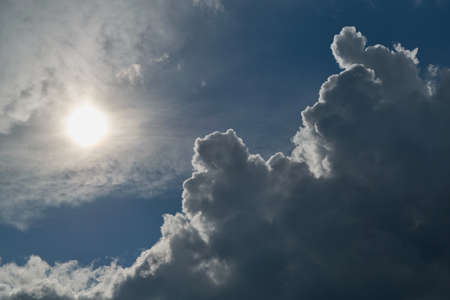 The sun shines brightly in the clear blue sky. Big storm clouds are coming. Cumulus clouds before rain looming on the sun and want his shield. Sunlight and rays illuminate the sky and clouds. Stock fotó