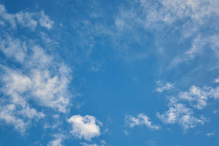 Small Cumulus and Cirrus clouds diverge from the center in different directions. In the middle is the empty space of a clear blue sky. Background, backdrop. Meteorology, weather forecast. Stock Photo