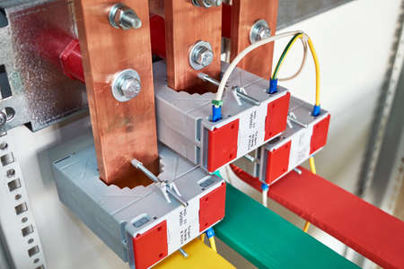 Electrical current transformers fitted on vertical copper busbars. Electrical wires are connected to the transformers. Copper tires are color-coded. The equipment is fixed in an electric Cabinet.
