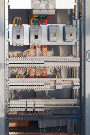 Large electrical switch Cabinet with circuit breakers and terminals. Several powerful and a lot of switches series modular switches. Cables and wires are connected to circuit breakers and buses.