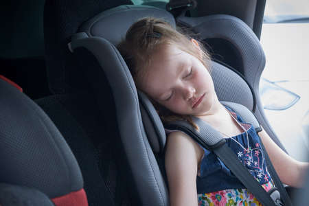 Little girl sleeps in a comfortable car seat for children. Soft and reliable car seat will save and save lives in a dangerous situation. The child put his head on the pillow of the chair and sleeping. Banco de Imagens