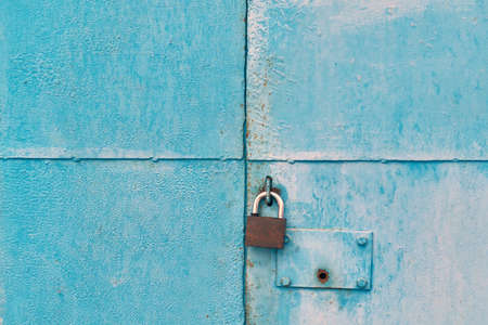The blue iron gate is closed with a padlock. On one door there is a round hole for the key of the hidden internal lock. The metal sheets of the doors are divided into four parts. Background, backdrop.