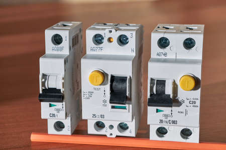 Electric circuit breaker, protective shutdown device, differential current circuit breaker lie in a row on the table. Devices to protect homes and buildings from short-circuit currents and human life. Stock Photo