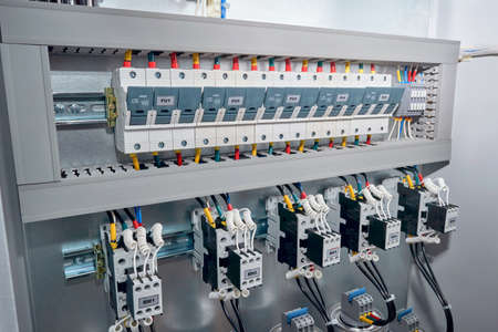 Series of Fuse holders, contactors or magnetic starters with front additional contacts, cylindrical capacitors in the electric reactive power compensation Cabinet. Wires are connected to the project.
