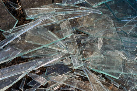 A pile of different sharp pieces of broken glass lying on the ground. Pieces of glass of different size and shape. Many pieces of oblong shape. The sharp edges glisten in the sunlight.