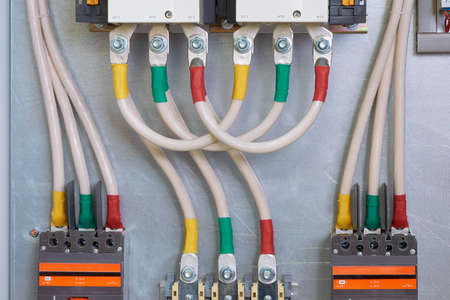 Connecting cables or wires to an industrial contactor or starter, circuit breakers and bolt-through terminals in an electrical Cabinet. The cables are connected in series and bent by a loop.