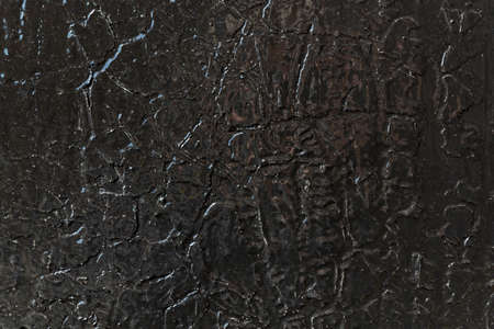 The surface of the wall is painted with black glossy oil paint over the old cracked and exfoliated. Surface of the dark paint is smoothed and shiny. Cracks in the form of lines of different shapes.