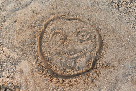 Smiley face painted on the sand with a finger. One eye winks and shows or stuck out tongue. Day, the sun is shining. Good mood, positive emotions. Rest, vacation. Friendship, good relations.
