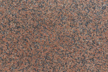 The flat surface of the granite slab is brown in speckled with black spots. Granite consists of crystals of stones of brown, red, black, gray color. Background, backdrop, texture.
