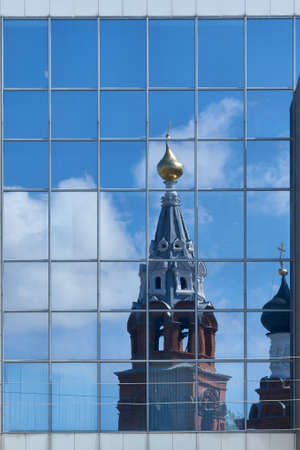 Reflection of the Christian Orthodox Church in mirrored glass on the modern building of the shopping center. Old Church with Golden domes, crosses and bell tower.