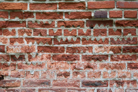 Old red brick wall of rectangular shape with triangular cutouts. Pieces of bricks partially broke off and cracked. Some bricks are of non-standard shape with cutouts of wavy shape.