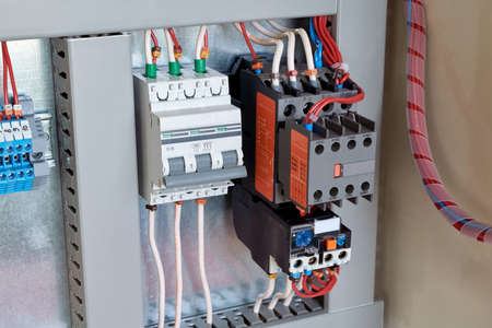 Circuit breaker, contactor or starter with additional contacts and thermal relay in electrical Cabinet. Electric control Cabinet for pumps or motors. The wires are connected to electrical equipment.