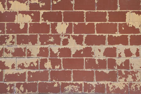The surface of the wall of the building is lined with rectangular tiles. The yellow paint on the tile was peeling and peeling from time to time. Tiles red-brown. Background, backdrop, texture.