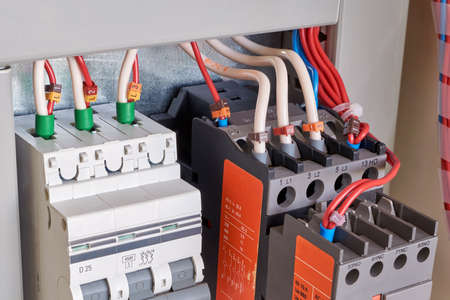 The wires are connected to electrical equipment. Circuit breaker, contactor or starter with additional contacts in electrical Cabinet. Electric control Cabinet for pumps or motors.