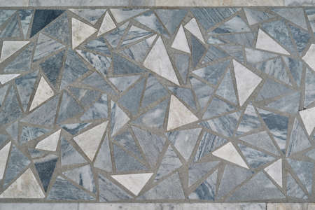The surface is lined with mosaic tiles of triangular shape and a variety of sizes. The triangles are arranged in a chaotic order. Banco de Imagens