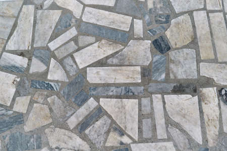 The surface is tiled with rectangular mosaic tiles of various sizes. The polygons are arranged in a chaotic order. Between tiles joints in concrete. Background, texture, background.