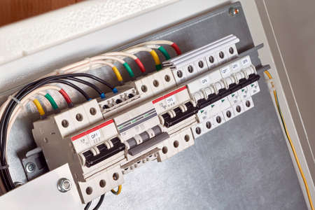 A series of modular circuit breakers in an electrical Cabinet with electrical wires or cables connected to them. The wires are color-coded. The modern distribution of electricity. Banco de Imagens