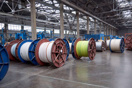 Several rows of large, heavy metal coils with electrical cables and wires in production. Modern line of automatic production of electric cable and wire. Coils on the concrete floor.