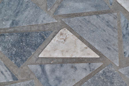 The surface of the triangular marble tiles. In the center of the white triangle, on the edges of the gray triangles. The triangles are arranged in a chaotic order. Background, texture, backdrop.
