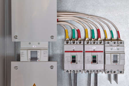 A large input circuit breaker and a series of circuit breakers with cables connected to them. Each phase of a wire or cable is color-coded. Electricity distribution. High current circuit breakers.