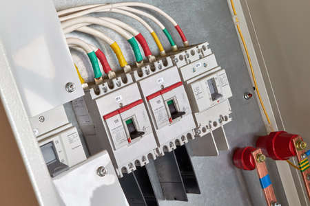 A number of power circuit breakers in the electrical Cabinet. White cables or wires are attached to the switches using cable lugs. Electricity distribution. High current circuit breakers. Banco de Imagens