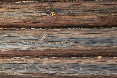 The surface of the wall or frame wooden house of logs brown. Seams between logs are compacted with tow, moss or wool. The logs have a wave pattern and cracks. Background, backdrop or Wallpaper. Banco de Imagens