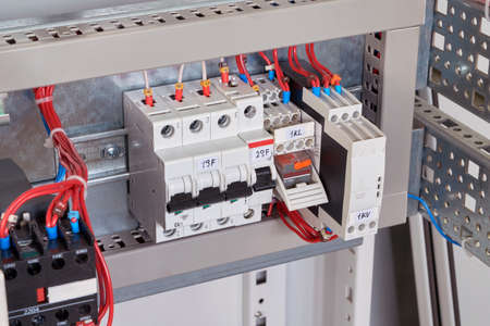 Circuit breakers, intermediate relay and phase control relay in the electrical Cabinet. Wires are connected to the electrical equipment according to the scheme. Automation of electrical equipment. Banco de Imagens