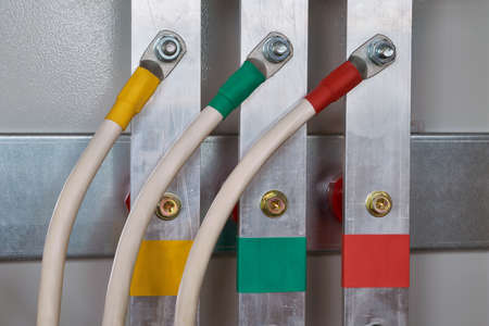 Three electric cable is connected to the vertical aluminum busbars in the electrical control panel by means of bolted connectors. Cables and busbars are color-coded. Electricity distribution.