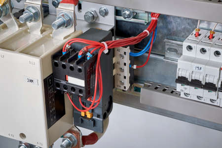 The electrical wires are connected to the side additional contacts of a powerful contactor or magnetic starter in the electrical Cabinet. Automation, uninterrupted power supply. Right circuit breaker.