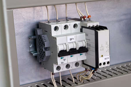 Modular circuit breaker and phase change control relay on the circuit Board in the electrical Cabinet. The devices are connected to the mains by electrical wires. Convenient and modern technology. Banco de Imagens