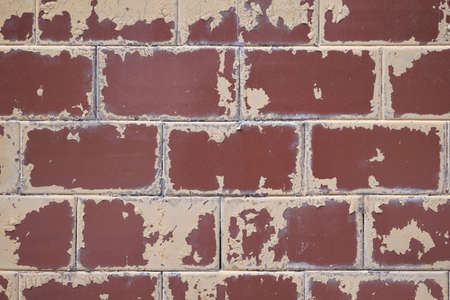 The surface of the wall is tiled with rectangular shape. The tile is painted with beige paint. Paint peeled off over time from weather conditions. Tiles are durable. Background or backdrop.