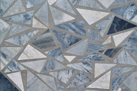 The surface of the wall or floor is made of triangular pieces of marble or granite. Triangular tiles of different sizes and colors are arranged in a chaotic order. Background or backdrop. Banco de Imagens