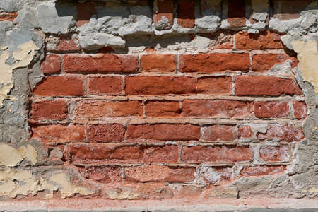 The brick wall of an old building with fallen plaster. Damaged by weather and time part of the wall of red brick. A space was formed with an oval frame with uneven edges. Background or backdrop.