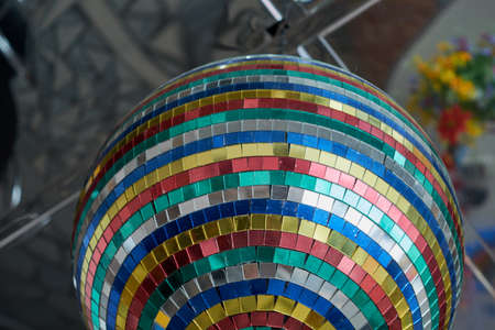 Mirror ball made from pieces of mirrors of different colors, size and shape. Pieces of mirrors square, rectangular, green, red, yellow, blue, white. A symbol of disco. Equipment for night clubs.
